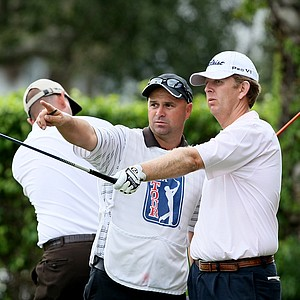 Michael Connell, right, talks with his caddie at No. 11 while Brenden Pappas practices his swing.