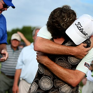 Troy Merritt gets a hug from his mom, Zoe Merrit, after coming off No. 18.