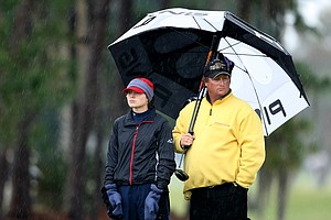 Candace Schepperle with her father/caddie David brave the freezing temperatures and rain.