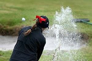 Taylore Karle ditches her shoes and socks to play a shot out of the water during the chilly final round of the Harder Hall.