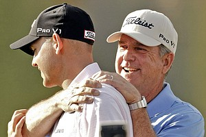 Bill Haas, left, is hugged by is dad, Jay Haas, after winning the 2010 Bob Hope Classic.
