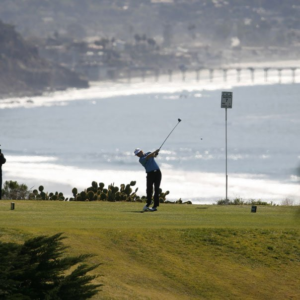 With the Pacific Ocean and the La Jolla, Calif., pier as a backdrop, Brandt Sedeker tees off on the seventh hole of North Course at Torrey Pines during his first-round 61 at the 2007 Buick Invitational.