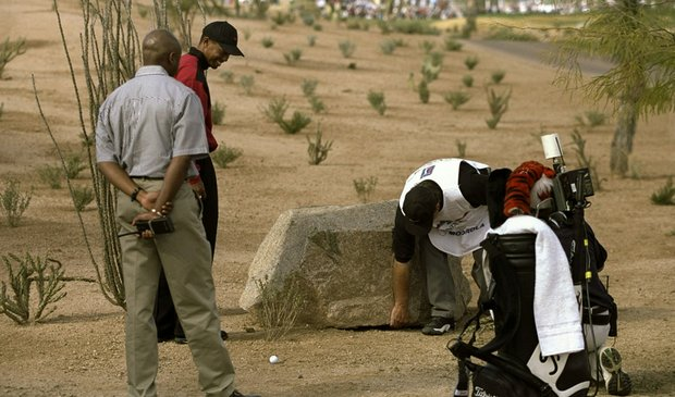 Caddie Fluff Cowen looks at a boulder near the ball of Tiger Woods during the 1999 Phoenix Open.