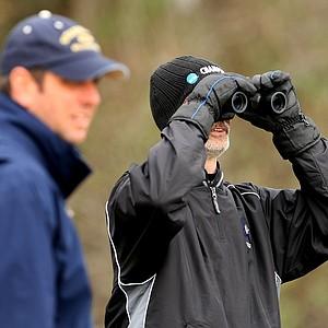 A bundled up John Hackney, head coach of Barton College checks the yardage at the par 3, No. 3.