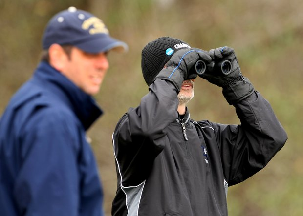 A bundled up John Hackney, head coach of Barton College checks the yardage at the par 3, No. 3.
