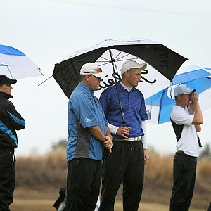 Taylor Johnson, center, of Lynn University, talks with his coach at No. 12 while trying to keep dry.