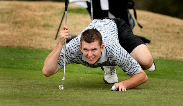 Dustin Yeager of Washburn University gets low to read a putt at No. 18.