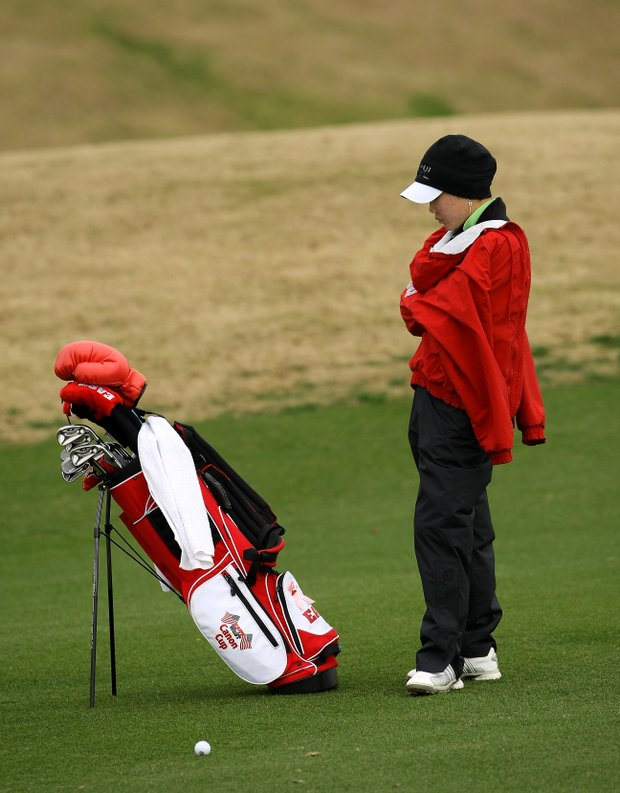 Karen Chung attempts to keep warm while waiting to hit her second shot at No. 9.