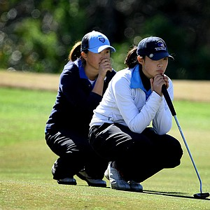 Suzie Lee (left) and Erynne Lee read their putts on the 18th green.