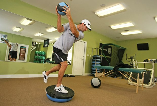 Dustin Johnson makes practice swings while standing on a balance disc.