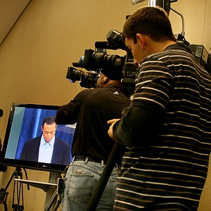 Media representatives from all around the world gather around flat screen TVs to watch Tiger Woods give his statement.