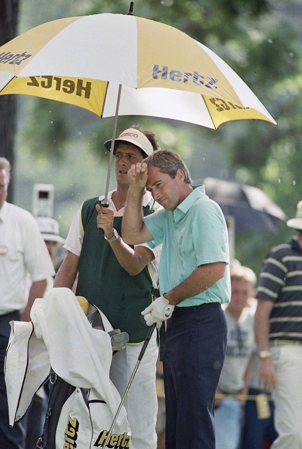 Caddie Greg Rita keeps Curtis Strange out of the elements during the 1988 U.S. Open.