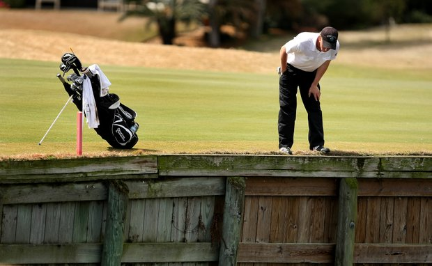 Coastal Carolina's Drew Ernst looks into the water where his ball entered at No. 18.