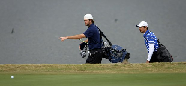 University of North Florida's J.C. Horne, left, tries to help Duke's Julian Suri find his plugged ball at No. 9.