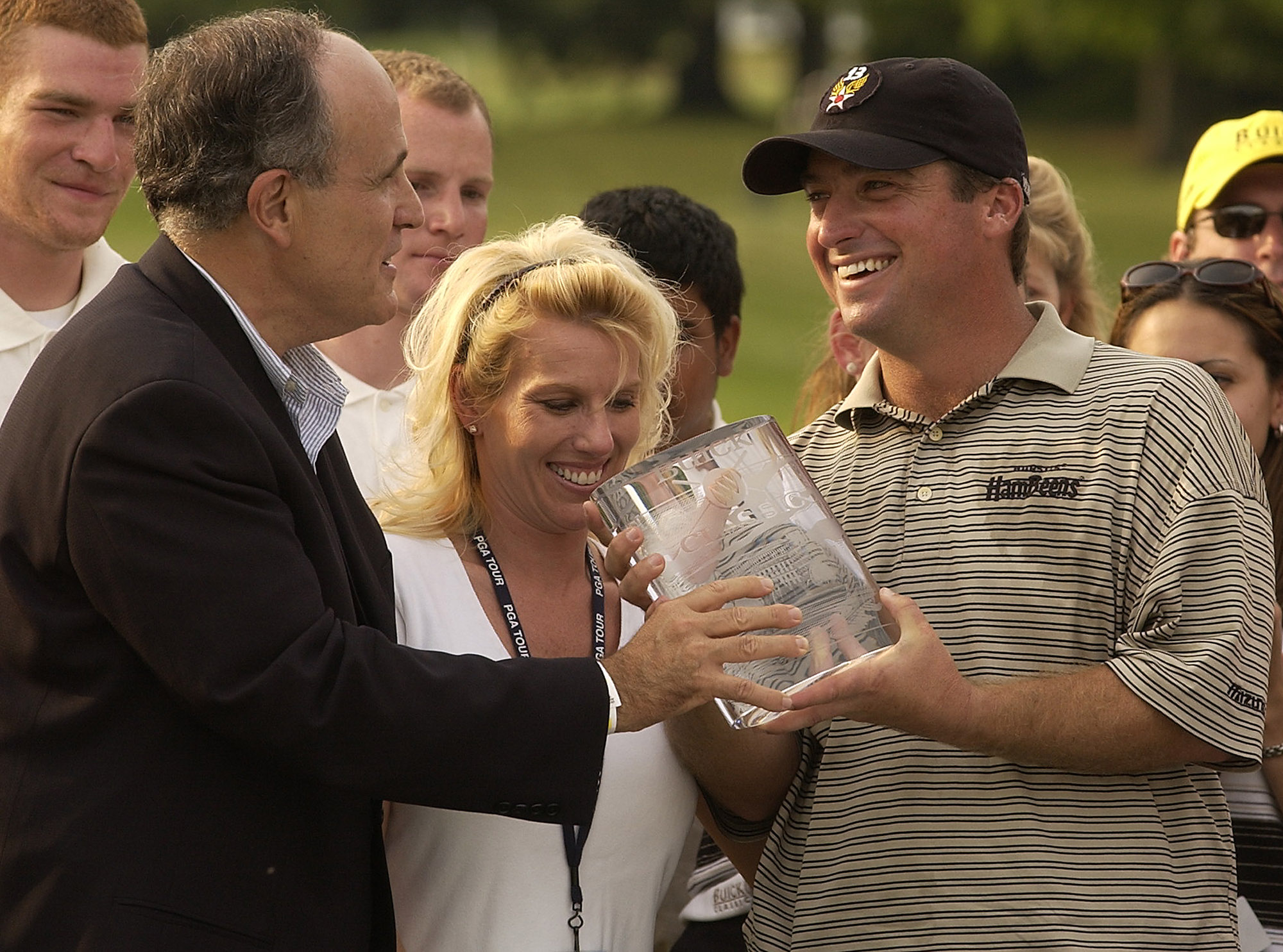 Chris Smith is presented with the trophy by former New York City Mayor Rudy Giuliani after winning the 2002 Buick Classic. His wife, Beth, looks on