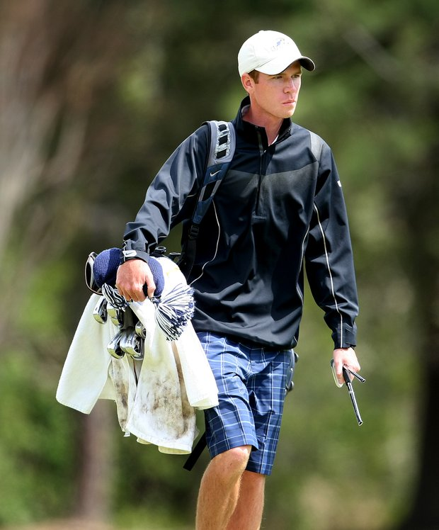 Kevin Aylwin of University of North Florida walks to No. 18 with a broken club after hitting out of the woods and snapping the club on a tree in his follow through.
