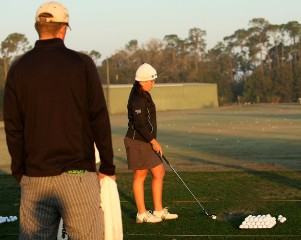 Former UCF player Stephanie Connelly warms up on the driving range in the early morning cold air.