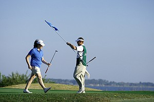 LPGA Commissioner Mike Whan replaces the flag at the third hole as Lauren Doughtie leaves the green.