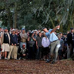 Jim Furyk hits his second shot from the woods which also strayed right.