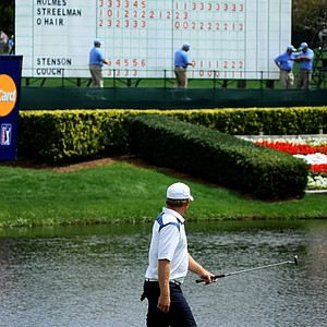 J. B. Holmes looks at the scoreboard as he walks down the 8th fairway. Holmes is tied for the lead after Round 1.
