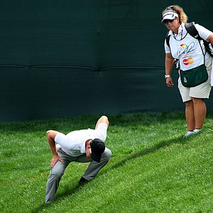 Henrik Stenson crouches low to look at his ball at No. 8 while his caddie Fanny Sunesson looks on. Stenson carded a 67 on Thursday.