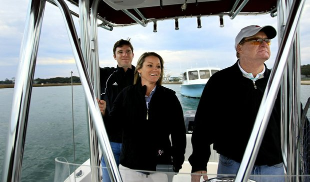 Kristy McPherson (center) and her brother Jared enjoy a ride with their father, David, on his fishing boat in Murrells Inlet.