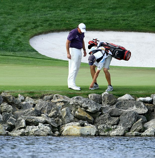 Phil Mickelson and his caddie look for Mickelson's ball at the 18th.