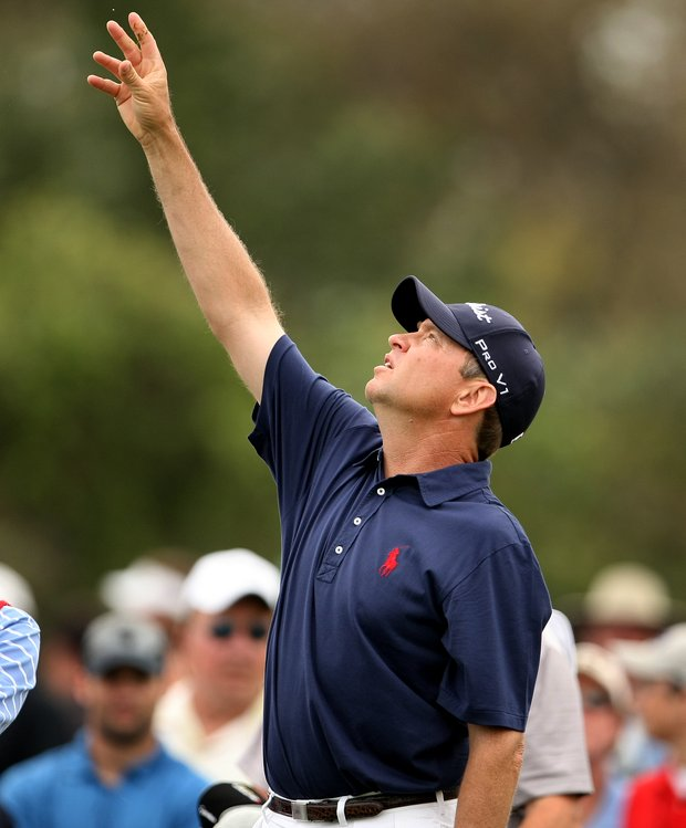 Davis Love III tosses grass to see what the wind is doing at No. 7.