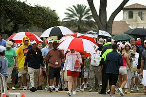 Spectators leave the area of the 18th green after a horn sounded halting play at 2:32 p.m. The final round will resume Monday at 10 a.m.