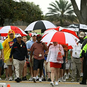 Spectators take cover as thunderstorms roll in Sunday at the Arnold Palmer Invitational.