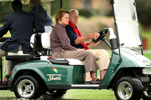 Arnold Palmer and his wife, Kit, ride through a water-logged 16th hole watching Ernie Els during the final round.
