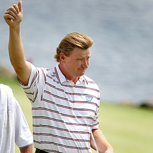 Ernie Els gives a thumbs up to the few spectators remaining at the rain delay Monday finish.