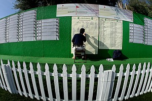 Eugene Inouye writes the scores of players near the putting green.
