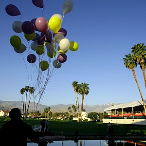 An usher with The Rock Church of Palm Desert, Diego Lyles, releases balloons during Easter Sunday Service on the 8th green.