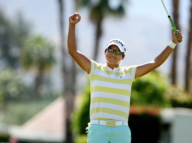 Yani Tseng raises her hands in victory after putting out to win by one shot over Suzann Pettersen.