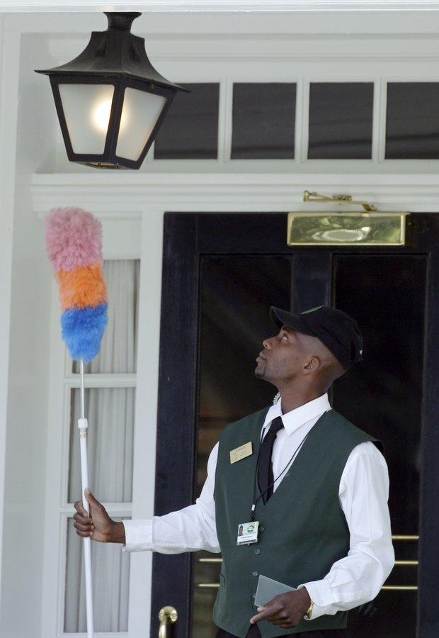 Warren Brown dusts the light outside of the champions locker room Sunday morning at Augusta National.