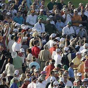 Tiger Woods tees off on Augusta National's first hole Monday during a practice round with Fred Couples.