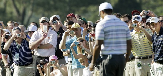 Tiger Woods walks down the first fairway Monday at Augusta National.
