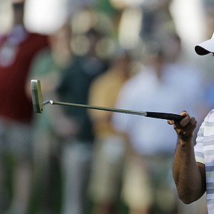 Tiger Woods lines up a putt during a practice round Monday at Augusta National.