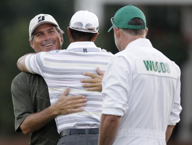 Fred Couples hugs Tiger Woods before a practice round Monday at the Masters.