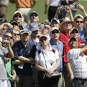 Spectators follow Tiger Woods' shot during his practice round Monday at Augusta National.