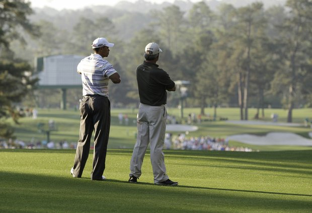 Tiger Woods talks with with Fred Couples in the second fairway during their Monday practice round at the Masters.