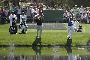 Francesco, left, and Edoardo Molinair and Matteo Manassero try to skip balls off the water Tuesday at Augusta's 16th.