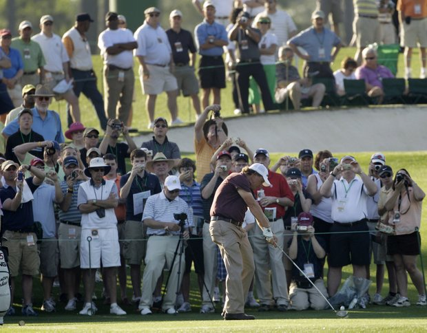 Phil Mickelson hits his tee shot in front of the crowd at the third hole.