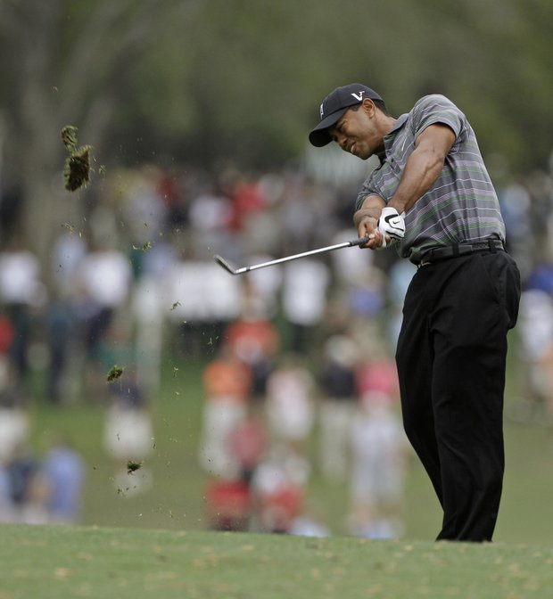 Tiger Woods plays his second shot into the par-4 first hole.