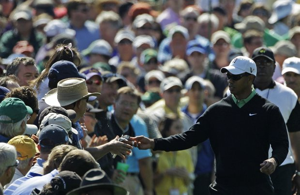 Tiger Woods hands his glove to a gallery member as he walks up the third hole.
