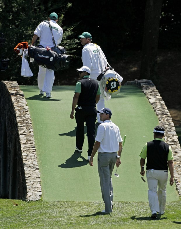 Tiger Woods, Matt Kuchar and K.J. Choi walk over the Hogan Bridge during the second round of the Masters.