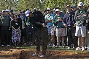Tiger Woods punches out from the rough at the first hole Friday.