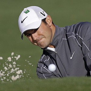 Trevor Immelman watches his chip shot out of a bunker on the second green.