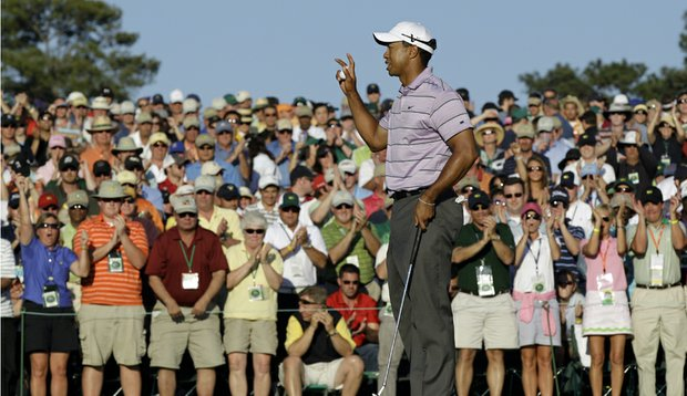 Tiger Woods waves to patrons at the 18th green Saturday after completing his third round.